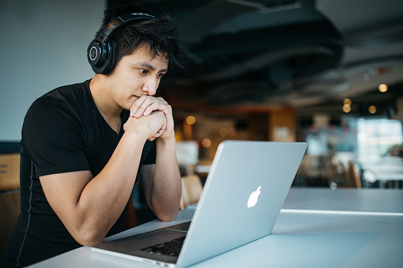 young-man-on-computer-listening-carefully